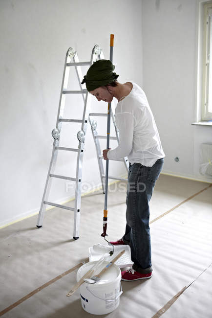 Woman preparing paint for painting walls — Stock Photo