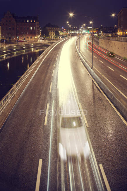 View of bridge with motion blurred cars and canal at night — Stock Photo
