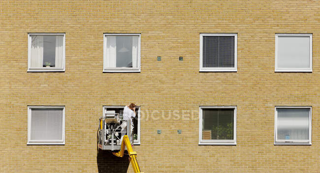 Rear view of working man against brick wall — Stock Photo