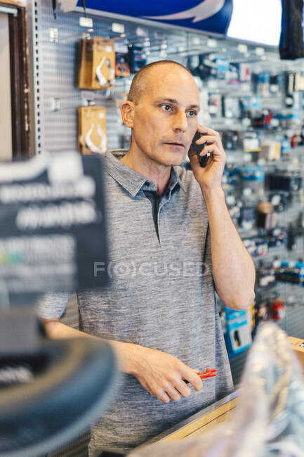 Small business owner of bicycle store talking by smartphone — Stock Photo