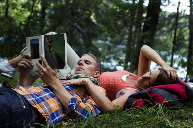 Caminhantes deitados na grama e livro de leitura, foco em primeiro plano — Fotografia de Stock