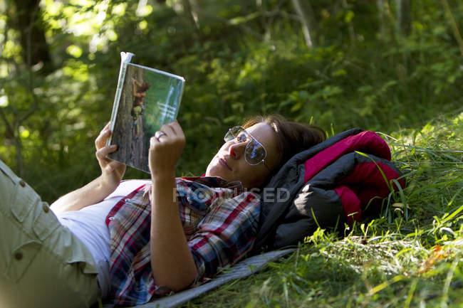 Caminhante feminina deitada na grama e guia de leitura — Fotografia de Stock