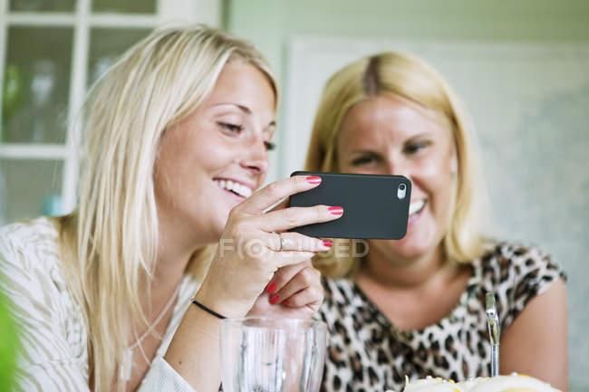 Молоді жінки роблять самовіддані, зосереджуються на передньому плані. — стокове фото