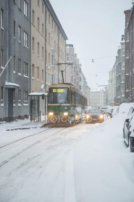 Трамвай та автомобіль на вулиці, вкритій снігом взимку — стокове фото