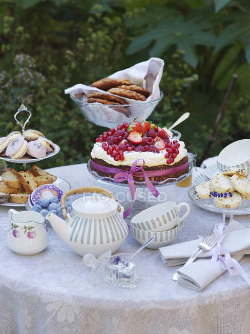 Mesa no jardim com bule e bolos com frutas de baga — Fotografia de Stock