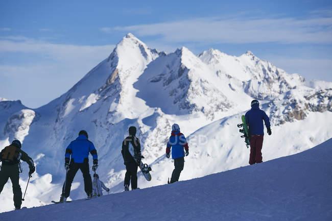 Люди на лыжах и сноуборде в горах — стоковое фото