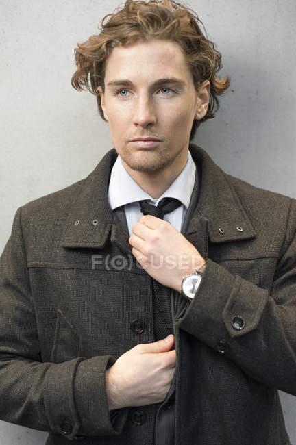 Homme d'affaires en manteau réglage cravate et à la recherche de suite — Photo de stock