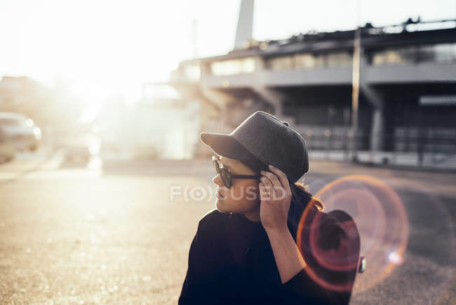 Woman adjusting sunglasses at sunset on parking lot — Stock Photo