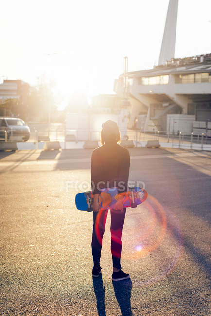 Rear view of female skateboarder looking at sunset on parking lot — Stock Photo