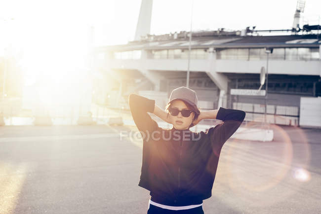 Portrait of woman in sunglasses with hands behind head at sunset — Stock Photo