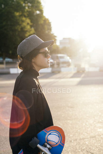 Side view of young woman with skateboard in sunglasses at sunset — Stock Photo