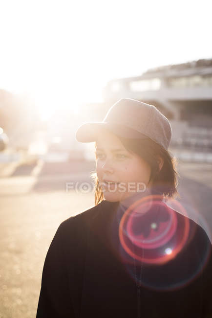 Young woman in cap looking away in soft light — Stock Photo