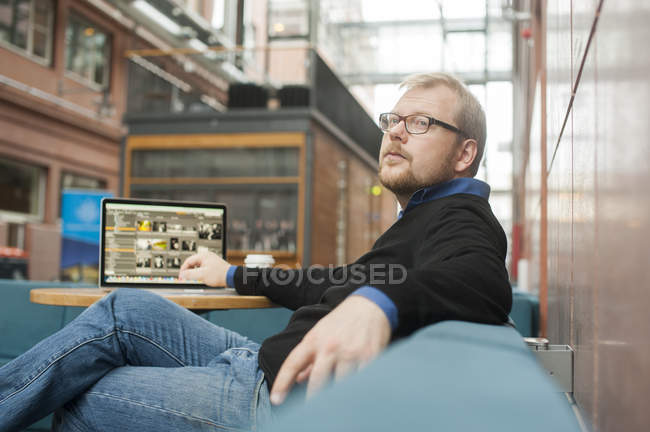 Homem adulto médio usando laptop, foco diferencial — Fotografia de Stock