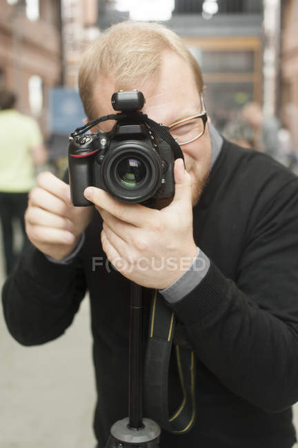 Mid adult man photographing on digital camera — Stock Photo