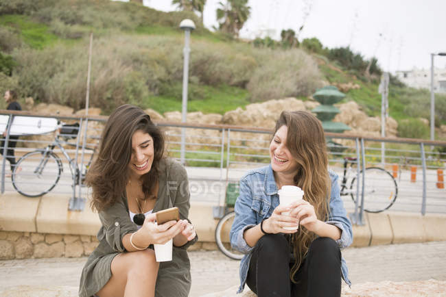 Women drinking coffee by promenade, focus on foreground — Stock Photo