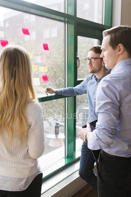 Kollegen, die sich Klebeschnotizen im Büro ansehen, selektive Fokussierung — Stockfoto