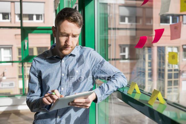 Businessman working on digital tablet indoors — Stock Photo