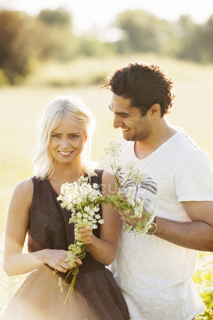 Couple at sunlit field, selective focus — Photo de stock