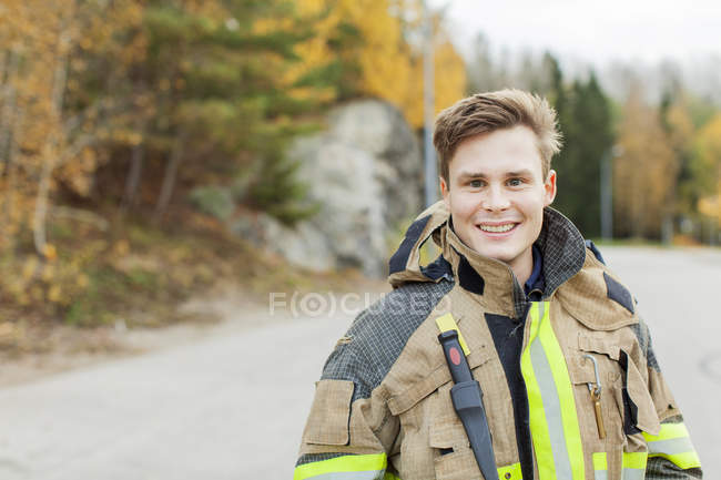 Firefighter looking at camera, focus on foreground — Stock Photo