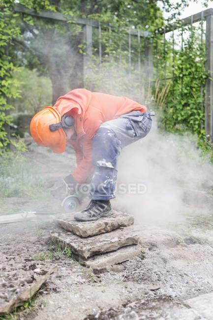 Worker cutting concrete blocks with circular saw — Stock Photo