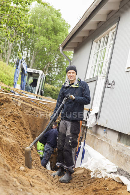 Portrait of young man with shovel standing in ditch by house wall — стоковое фото