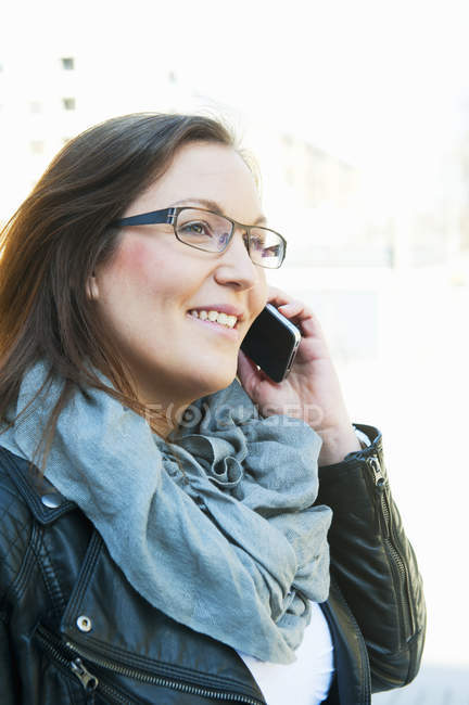 Woman with brown hair, with glasses talking on phone — Stock Photo