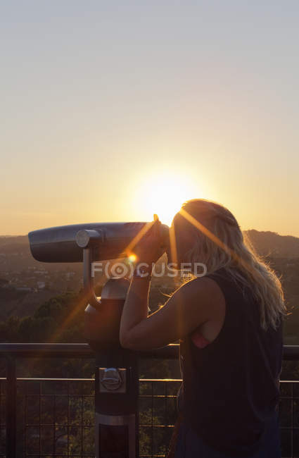 Woman using coin-operated binoculars at sunset in Los Angeles — Stock Photo
