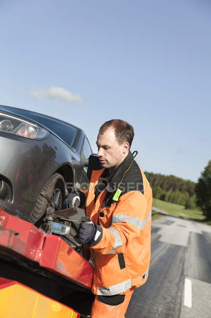 Man in protective workwear working on car to be towed — Stock Photo