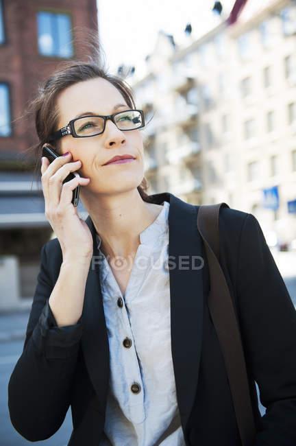 Деловая женщина разговаривает по телефону и глядя — стоковое фото