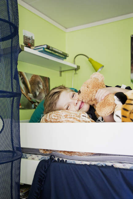 Boy in bed with teddy bear, selective focus — Foto stock