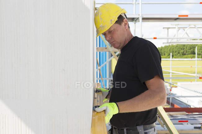 Construction worker using spirit level — Stock Photo