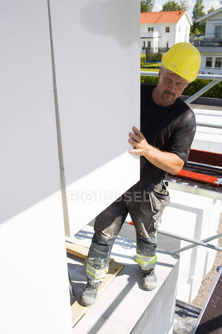 Construction worker adjusting building blocks to build wall — Stock Photo