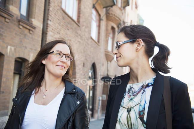 Due donne che camminano lungo la strada e si guardano — Foto stock