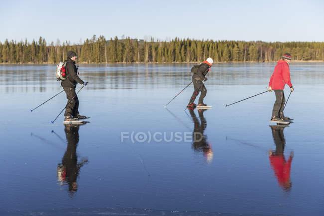 Mature people ice skating on frozen lake — Stock Photo