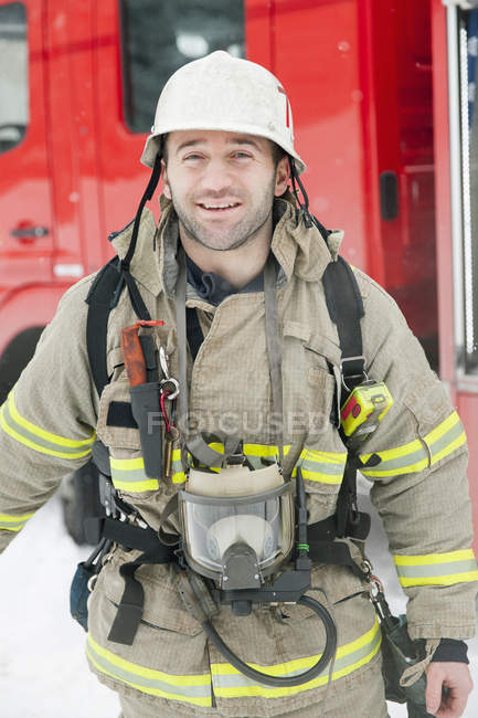Portrait of firefighter in front of fire engine — Stock Photo