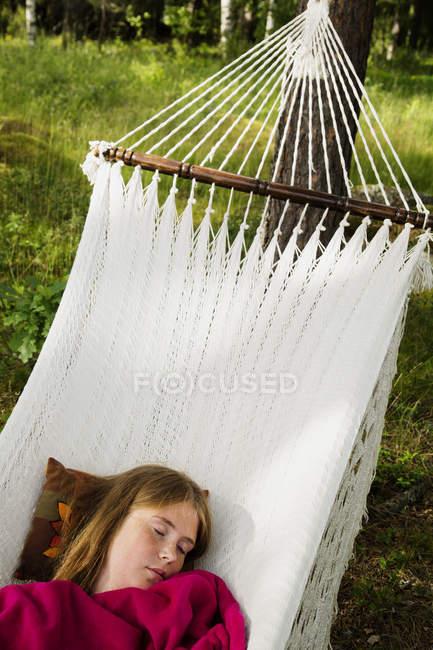 Молодая женщина лежит на гамаке в лесу — стоковое фото