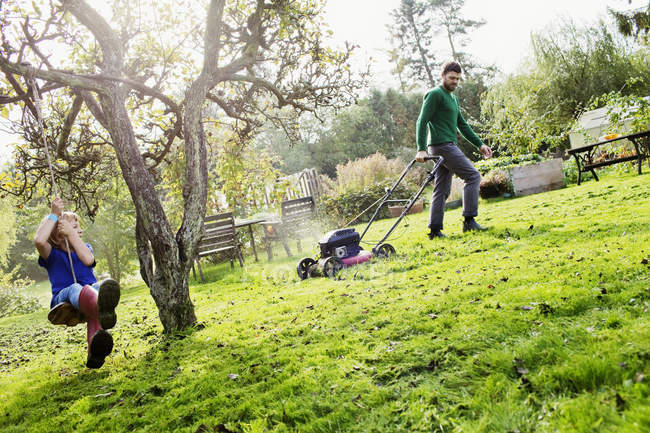 Father and son in domestic garden — Stock Photo