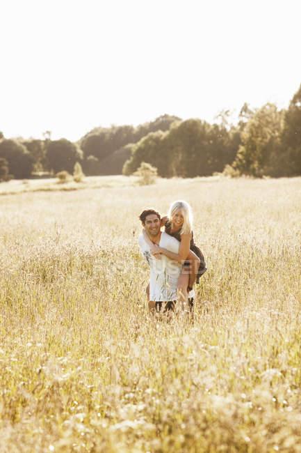 Jovem casal equitação piggyback no prado — Fotografia de Stock