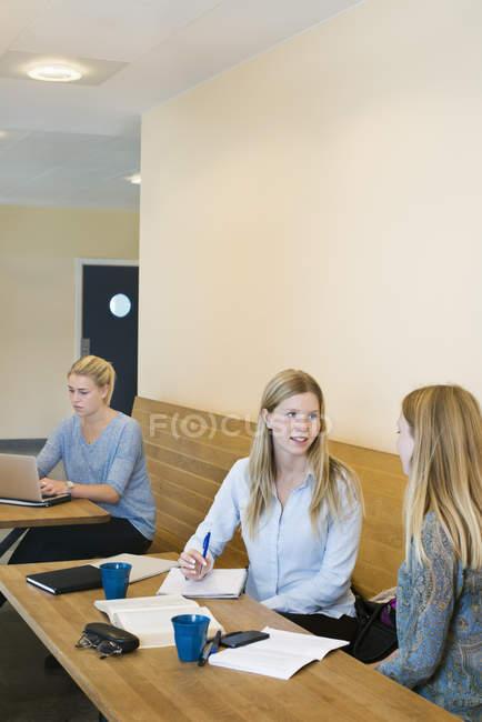 Junge Frauen mit Laptop und im Auditorium der Universität studieren — Stockfoto