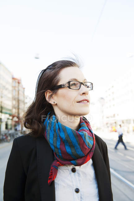 Woman with brown hair, with glasses looking away — Stock Photo