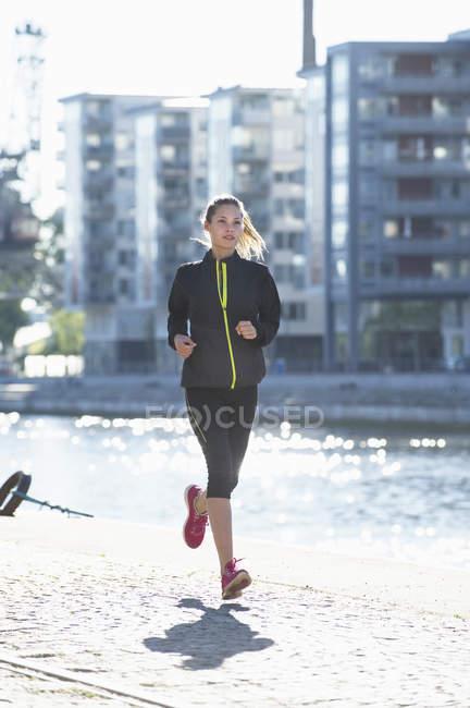 Woman in sportswear running along embankment — Stock Photo