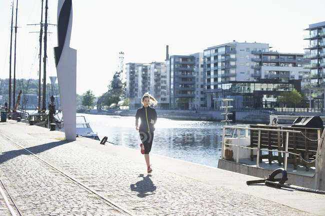 Женщина с каштановыми волосами бежит вдоль набережной — стоковое фото