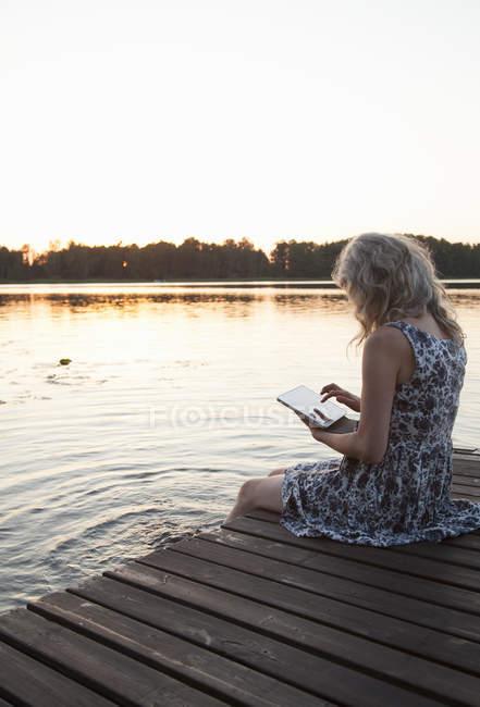 Femme assise sur la jetée et utilisant une tablette numérique — Photo de stock