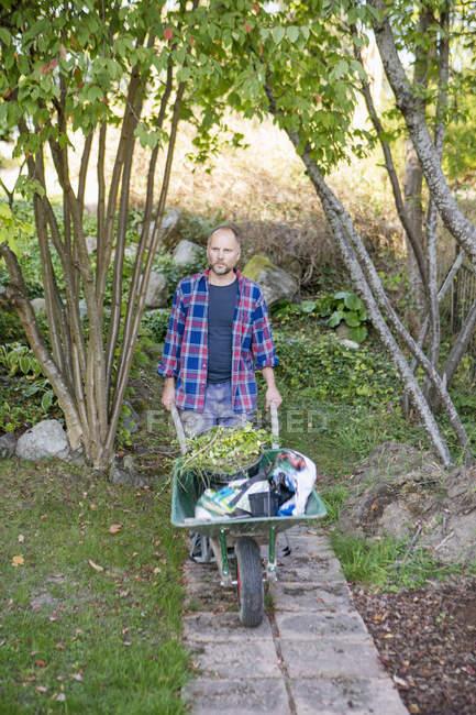 Vorderansicht des Menschen drängen Schubkarre im Garten — Stockfoto