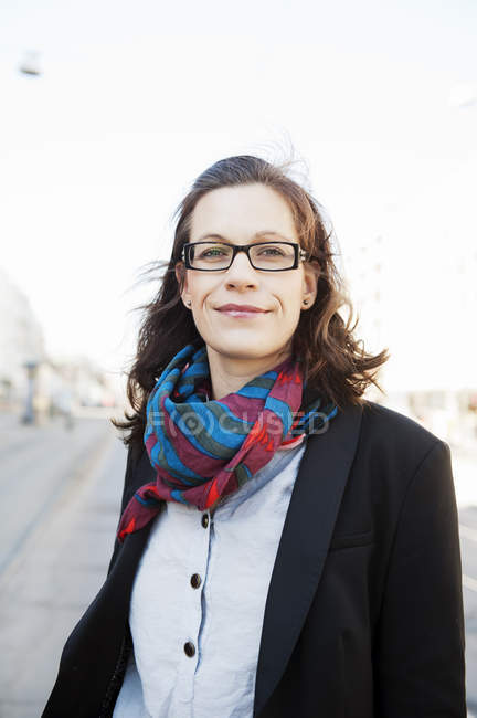 Woman with brown hair, with glasses standing on street — Stock Photo