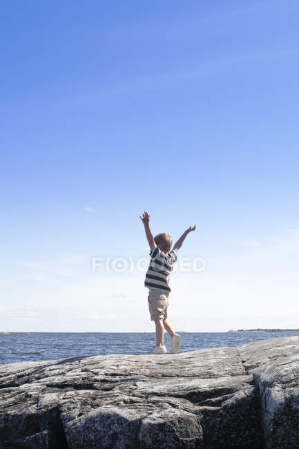 Boy standing on seaside and looking at view — Stock Photo