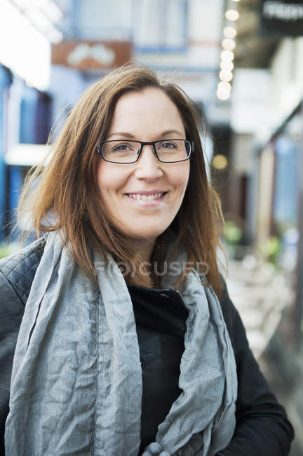 Woman with brown hair, with glasses looking at camera — Stock Photo