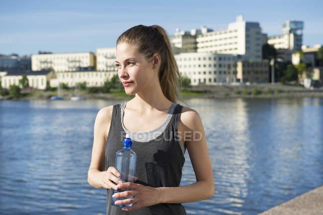 Donna in piedi con bottiglia d'acqua in mano — Foto stock