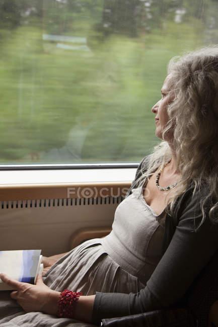 Vue de côté de femme regardant par la fenêtre en train — Photo de stock