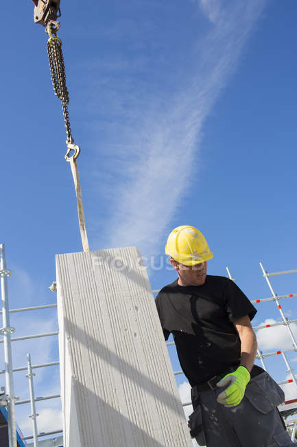 Construction worker preparing building block to be lifted — Stock Photo
